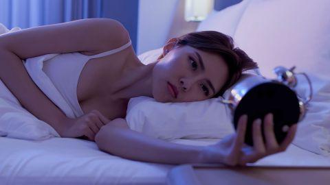 Eine Frau liegt im Bett und schaut auf einen Wecker, den sie in der Hand hält.