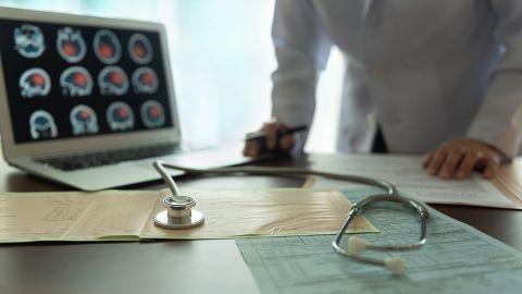 Schlaganfall: Ein Arzt analysiert ausgedruckte Berichte, die neben einem Stethoskop auf einem Tisch liegen. Ein Laptop-Bildschirm zeigt Bilder eines gescannten Schädels und Gehirns.