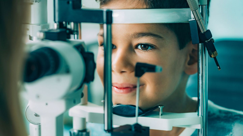 Schwachsichtigkeit bei Kindern: Ein Junge sitzt vor einer Spaltlampe im Behandlungsraum einer Augenarztpraxis und lässt die Sehstärke seiner Augen testen.