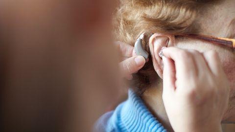 Schwerhörigkeit und Gehörlosigkeit: Ein Mann setzt einer älteren Frau ein Hörgerat ins Ohr.
