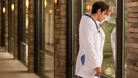 Behandlungsfehler: Ein junger Arzt steht an einem Fenster. Er hat die Augen geschlossen und stützt seinen gesenkten Kopf auf den linken Unterarm, der an der Fensterscheibe lehnt.
