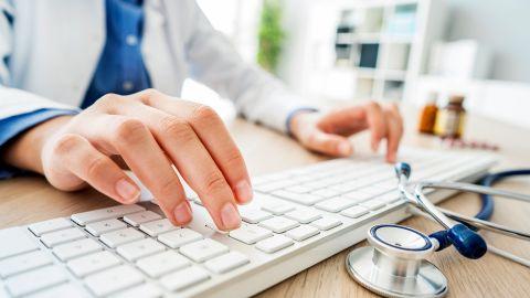 Zweitmeinung: Eine Ärztin sitzt an einem Schreibtisch und tippt mit den Fingern beider Hände auf eine Computertastatur. Neben der Tastatur liegt ein Stethoskop.