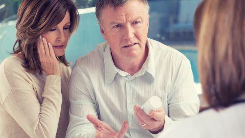 Beschwerde über ärztliche Behandlung: Ein Mann und eine Frau stehen dicht beinander, eine Ärztin steht ihnen gegenüber. In einer Hand hält der Mann ein Medikament. Er schaut die Ärztin fragend an.