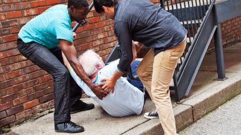 Stürze bei älteren Menschen: Zwei Männer stehen vor einer Treppe und stützen mit ihren Händen einen älteren Mann, der mit seinem Gesäß auf einem Gehweg sitzt und seinen Oberkörper nach vorne gebeugt hat. Die Beine des Senioren berühren die Treppenstufen.