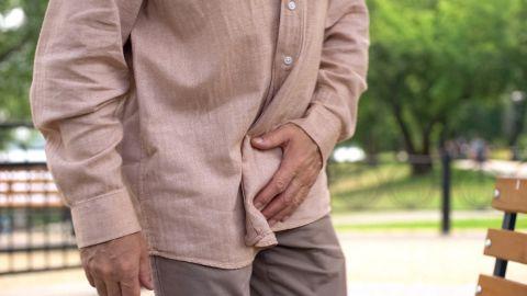 Varikozele: Ein Mann steht leicht nach vorne gebeugt und fasst sich mit einer Hand an sein Becken.