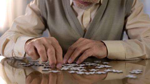 Ein älterer Herr sitzt an einem Tisch und puzzelt.