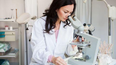 Vulvakarzinom: Eine Ärztin sitzt in einem Labor und schaut durch ein Miskroskop.