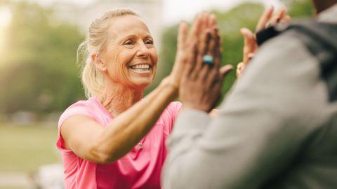 Wechseljahre: Eine Frau mittleren Alters trägt sportliche Kleidung und klatscht ihre Handflächen in die Handflächen der anderen Frau.