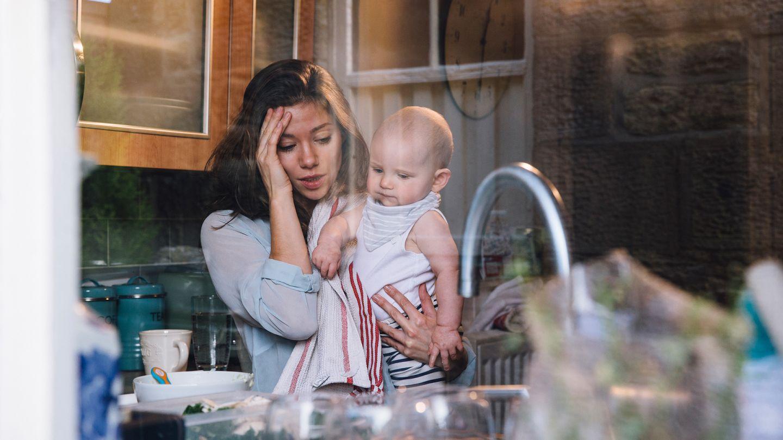 Wochenbettdepression: Eine gestresst wirkende Frau steht in der Küche, hält ein Baby im Arm und hält sich den Kopf.